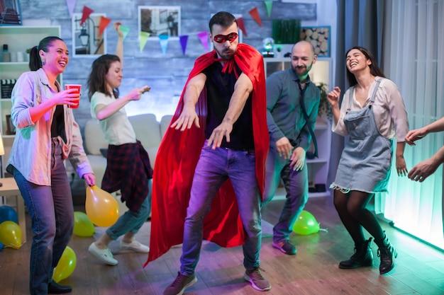 Fröhlicher mann im superheldenkostüm, der seine tanzbewegungen auf der party von freunden zeigt.