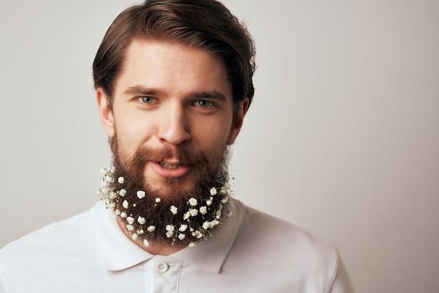 Fröhlicher mann im weißen t-shirt blumen in bartdekoration abgeschnittene ansicht