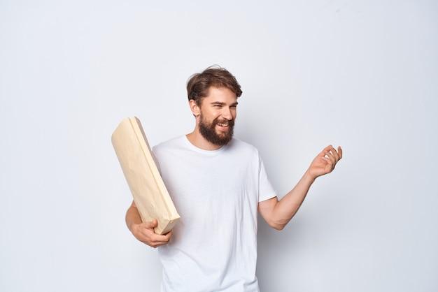 Fröhlicher mann im weißen t-shirt mit papiertüte, die hellen hintergrund verpackt
