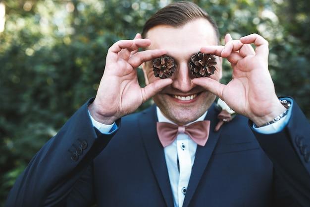 Fröhlicher mann in anzug posiert mit zapfen