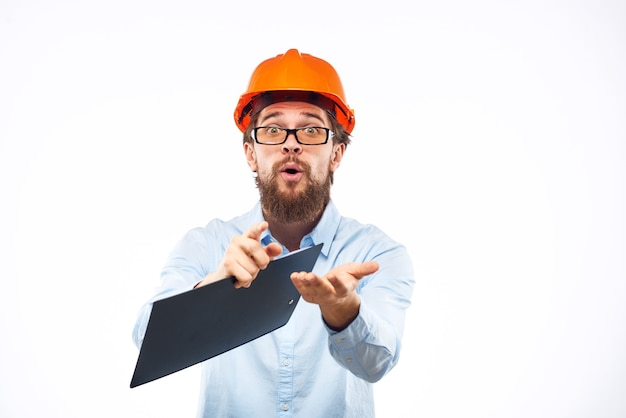 Fröhlicher mann in der orangefarbenen schutzhelmkonstruktion dokumentiert serviceprofis.