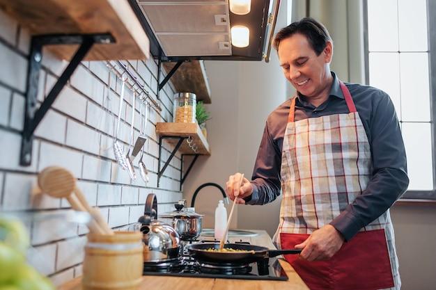 Fröhlicher mann in der schürze stehen am herd und kochen essen. er lächelt und mischt zutaten. mann allein dort stehen.