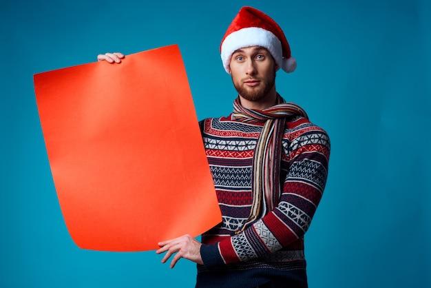Fröhlicher mann in einem weihnachtlichen orange mockup-plakat auf blauem hintergrund