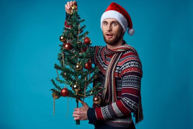 Fröhlicher mann in einem weihnachtsmann-hut, der ein banner-feiertagsstudio posiert. foto in hoher qualität