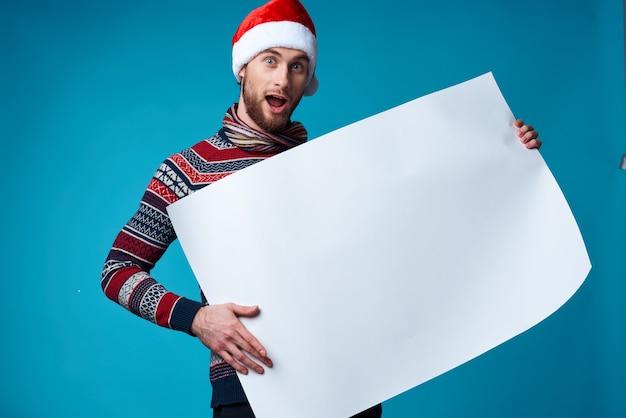 Fröhlicher mann in einer weihnachtsmütze, der einen blauen hintergrund des fahnenurlaubs hält