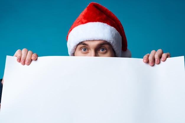 Fröhlicher mann in einer weihnachtsmütze, der einen isolierten hintergrund mit bannerfeiertag hält
