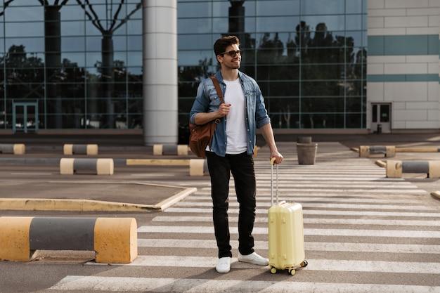 Fröhlicher mann in jeansjacke und schwarzer hose hält gelben koffer und braunen rucksack