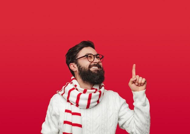 Fröhlicher mann in warmen hellen strickwaren, die nach oben zeigen