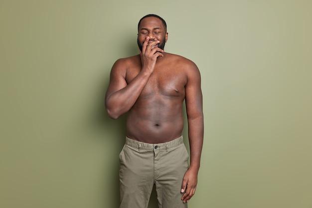 Fröhlicher mann lacht positiv bedeckt mund mit der hand hört etwas lustiges trägt hosen zeigt nackten oberkörper hat muskulöse arme posiert gegen khaki studiowand