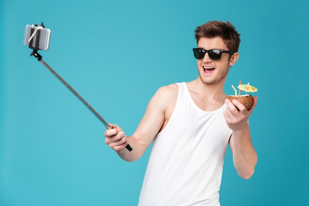 Fröhlicher mann machen selfie mit cocktail per telefon.