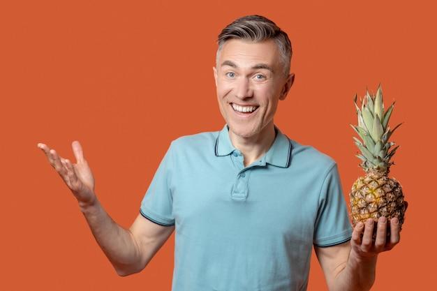 Fröhlicher mann mit ananas in der hand