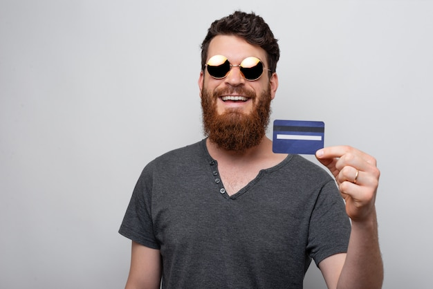 Fröhlicher mann mit bart, der blaue kreditkarte über grauem hintergrund hält