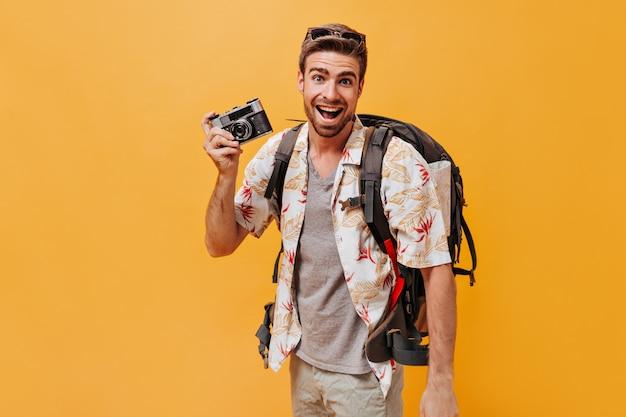 Fröhlicher mann mit bart in grauem t-shirt und bedrucktem hellem hemd lächelt und posiert mit kamera und rucksack an oranger wand