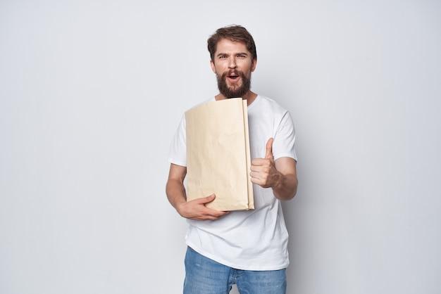 Fröhlicher mann mit bartpapier-basteltüten, die einkaufen verpacken