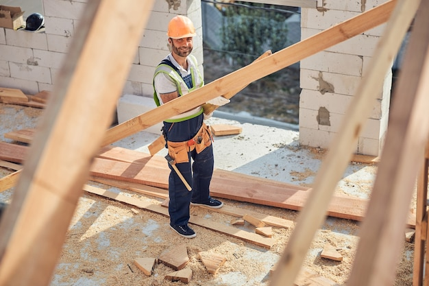 Fröhlicher mann mit bauausrüstung und werkzeuggürtel, während er ein langes stück bauholz hält holding