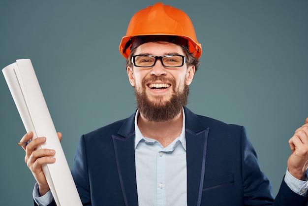 Fröhlicher mann mit blaupausen in den händen im orangefarbenen helm-sicherheitsingenieur