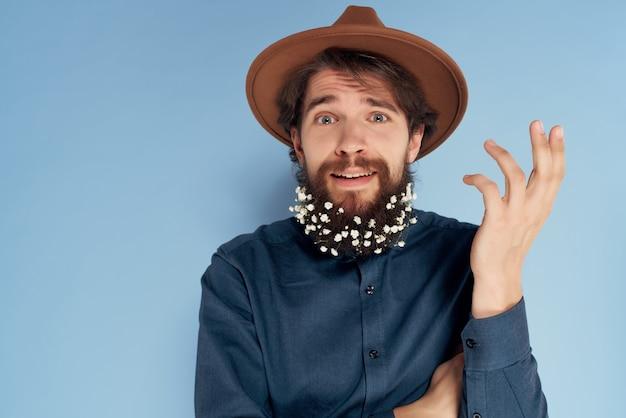 Fröhlicher mann mit blumen in einem bart in einem hut nahaufnahme blauem hintergrund Premium Fotos