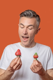 Fröhlicher mann mit erdbeere in den händen