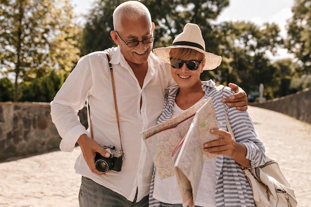 Fröhlicher mann mit grauem haar in hellem hemd und jeans mit kamera lächelnd und betrachten karte mit blonder dame im hut und im blauen outfit im park.