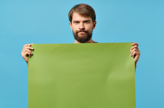 Fröhlicher mann mit grünem mockup-poster rabatt copyspace studio