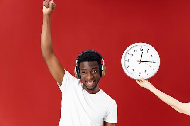 Fröhlicher mann mit kopfhörern hört musik neben dem uhrzeiger über seinem kopf. foto in hoher qualität