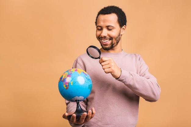 Fröhlicher mann mit linse, die den globus mit liebe und sorgfalt lokalisiert über beige hält