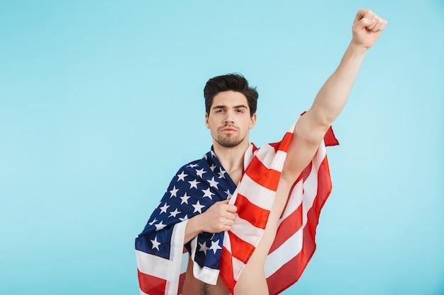Fröhlicher mann mit nacktem oberkörper, der isoliert steht, amerikanische flagge trägt und erfolg feiert