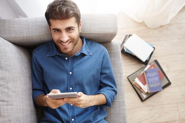 Fröhlicher mann mit stoppeln, genießt online-kommunikation