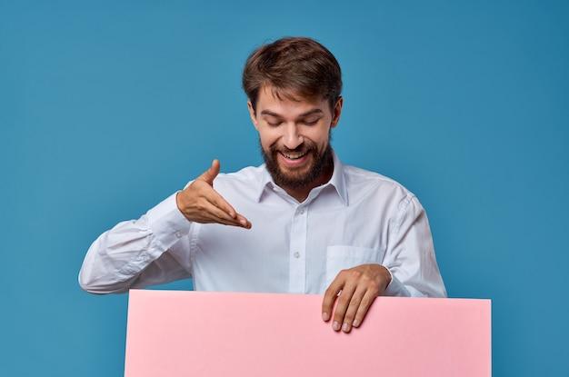 Fröhlicher mann rosa banner in der hand leeres blatt präsentation blauer hintergrund. foto in hoher qualität