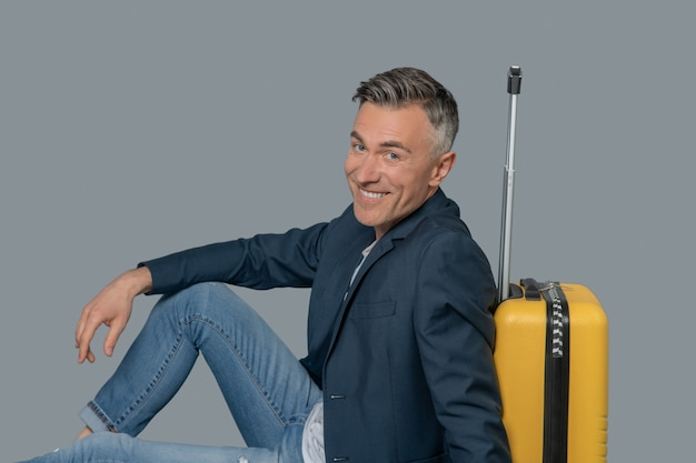 Fröhlicher mann sitzt auf dem boden in der nähe von koffer