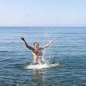 Fröhlicher mann spritzt allein auf see im wasser