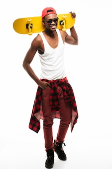 Fröhlicher mann stehend und hält skateboard