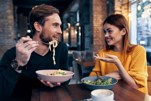 Fröhlicher mann und frau, die in einem café sitzen, das kommuniziert