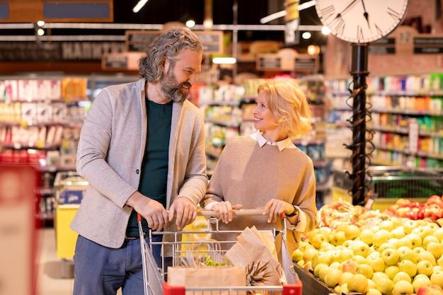 Fröhlicher mann und frau im alter schauen sich an, während sie wagen mit nahrungsmitteln während ihres besuchs im supermarkt schieben