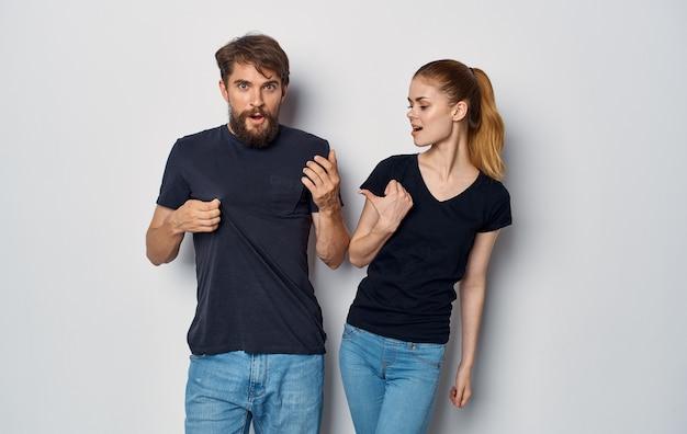 Fröhlicher mann und frau in schwarzen t-shirts studio freizeitkleidung