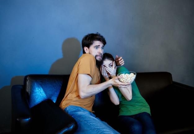 Fröhlicher mann und frau sitzen auf der couch und schauen filme popcorn familienurlaubcorn