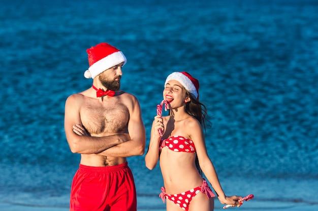 Fröhlicher mann und mädchen in weihnachtsmützen halten weihnachtslutscher.