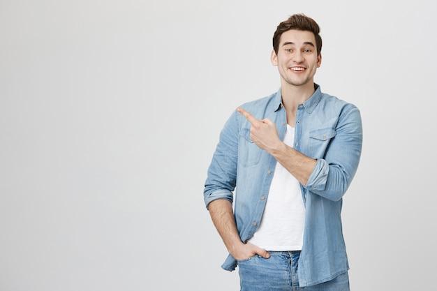Fröhlicher mann zeigt mit dem finger nach links, wirbt für das produkt