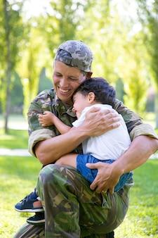 Fröhlicher militärvater umarmt kleinen sohn und hält jungen in den armen im freien, nachdem er von der missionsreise zurückgekehrt ist. vertikaler schuss. familientreffen oder rückkehr nach hause konzept