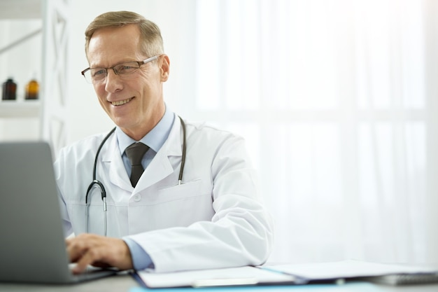 Fröhlicher mitarbeiter des gesundheitswesens mit laptop in der klinik