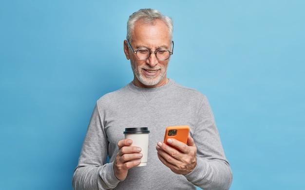 Fröhlicher moderner älterer mann verwendet handy für kommunikationstypen textnachricht auf telefonbildschirm hält pappbecher kaffee rollt internetseiten, gekleidet in freizeitkleidung, isoliert über blauer wand