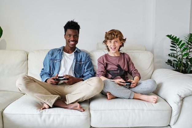 Fröhlicher multiethnischer mann und junge, die zusammen videospiele spielen