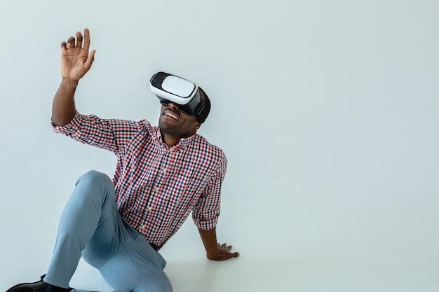 Fröhlicher netter afroamerikanischer mann, der vr-brille testet, während er auf dem boden sitzt