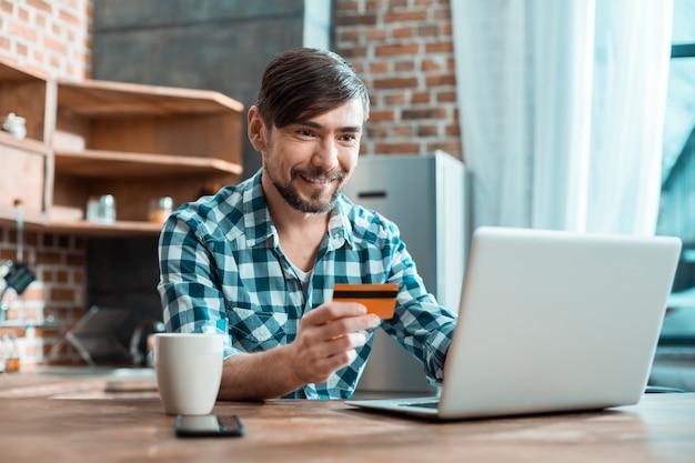 Fröhlicher netter gutaussehender mann, der vor seinem laptop sitzt und eine kreditkarte hält, während er online-banking verwendet