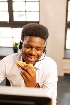 Fröhlicher netter mann, der ein sandwich isst, während er im callcenter arbeitet