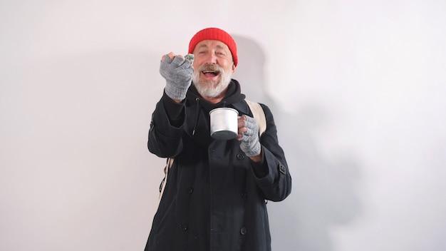 Fröhlicher obdachloser alter mann mit einem bart in einem hut grinste und hielt geld in seiner hand auf einem isolierten hintergrund