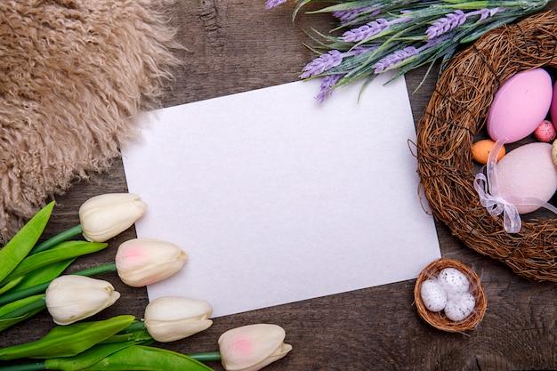 Fröhlicher osterrahmen mit grußkarte für text, eier, schleifen und blumen auf hölzernem hintergrund. ostergrußkarte.
