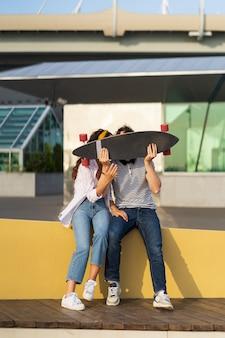 Fröhlicher paarkuss, der sich über dem longboard versteckt, ein verspielter mann und eine verliebte frau halten zusammen skateboard