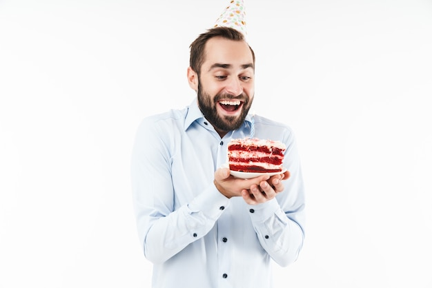 Fröhlicher partymann lächelt und hält geburtstagstorte mit kerze isoliert über weißer wand