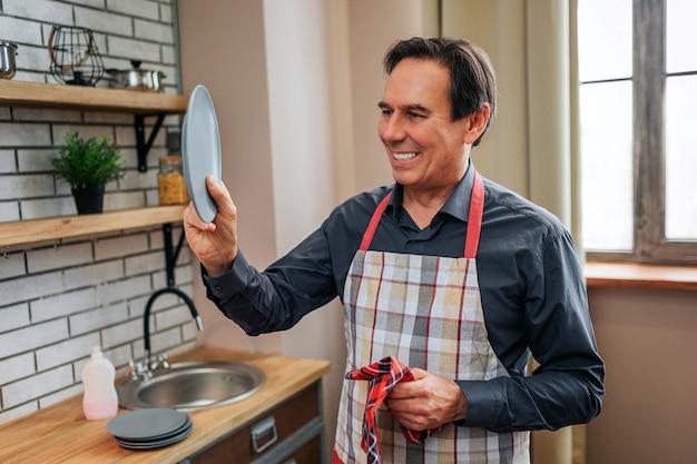 Fröhlicher positiver mann steht allein in der küche. er alter teller und schau es dir an. mann lächelt. er trocknete es mit einem handtuch.